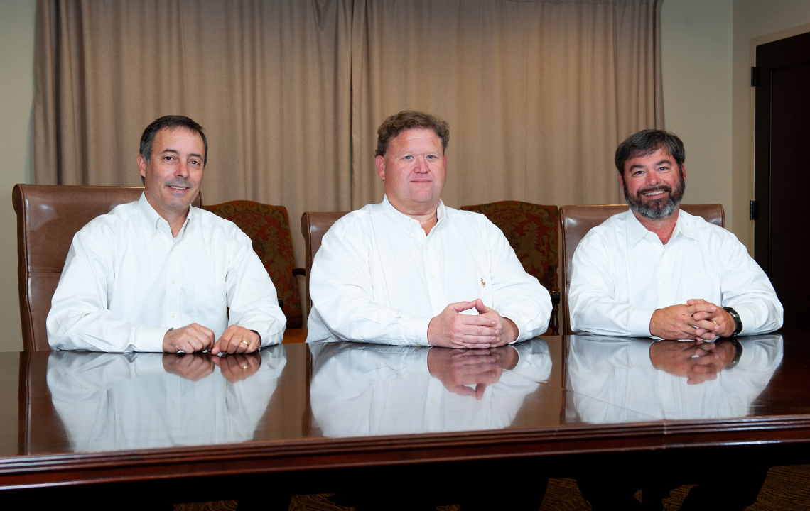 ELM Executive Team - Robert Petro, Joe Collins and Clark Winsor in white shirts sitting in desk chairs at a meeting table